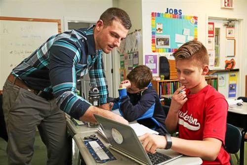 Teacher working with student on computer
